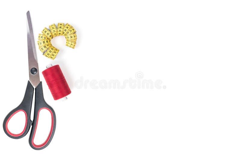 Cosiendo suministra las tijeras grandes la manija negra, el hilo de coser rojo y la cinta métrica amarilla en un fondo blanco Tex imágenes de archivo libres de regalías
