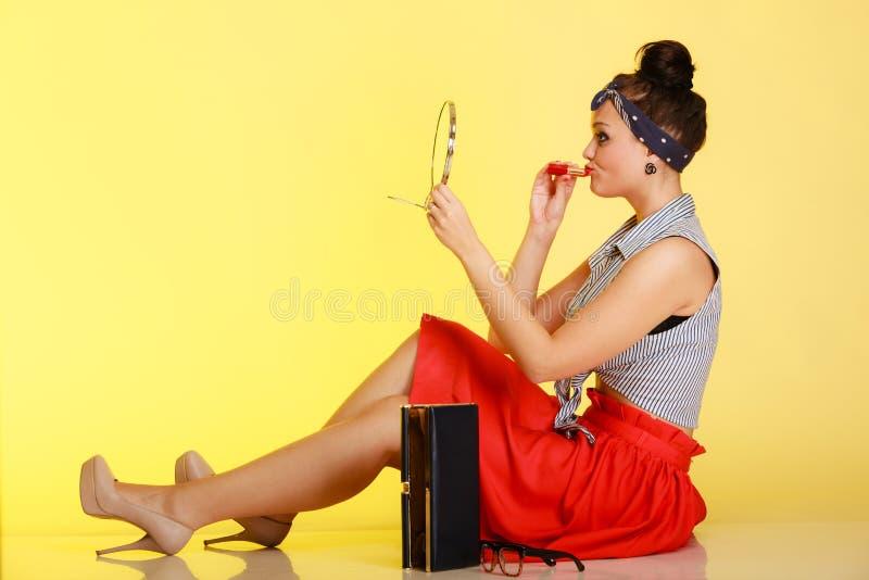 Cosmético. Mujer de la muchacha Pin-para arriba con el bollo que aplica maquillaje en amarillo. fotografía de archivo