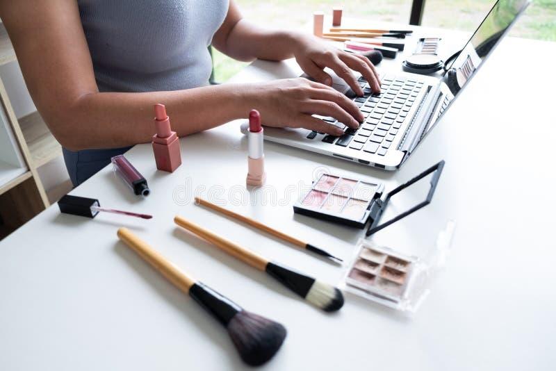 Cosméticos atuais da beleza do blogger da beleza que sentam-se na tabuleta dianteira A revisão asiática bonita dos cosméticos do  fotos de stock royalty free