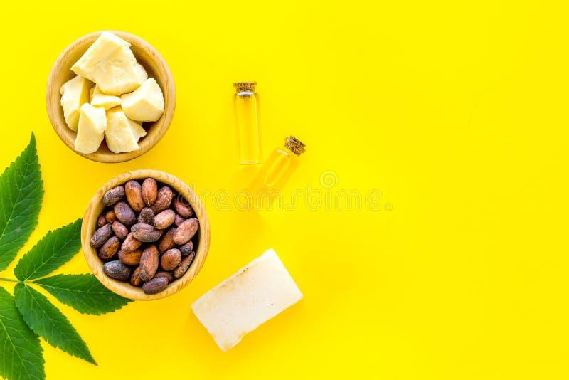 Cosméticos con la manteca de cacao para el cuidado de piel Granos de cacao y manteca de cacao en cuenco, jabón, aceite o la loció foto de archivo libre de regalías