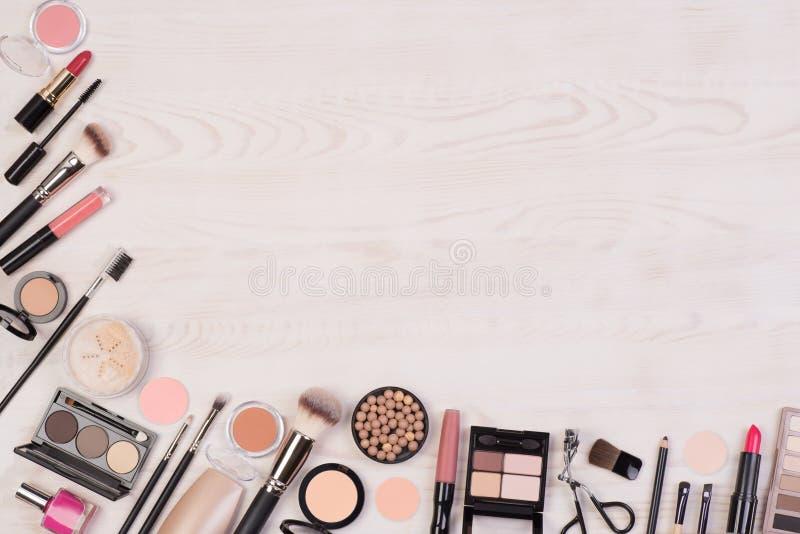 Cosméticos da composição tais como sombras, batom, rímel e acessórios da composição no fundo branco, de madeira, vista superior c fotos de stock