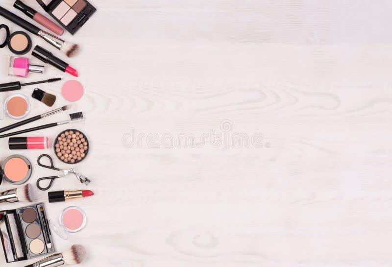 Cosméticos da composição tais como sombras, batom, rímel e acessórios da composição no fundo branco, de madeira, vista superior c fotografia de stock royalty free