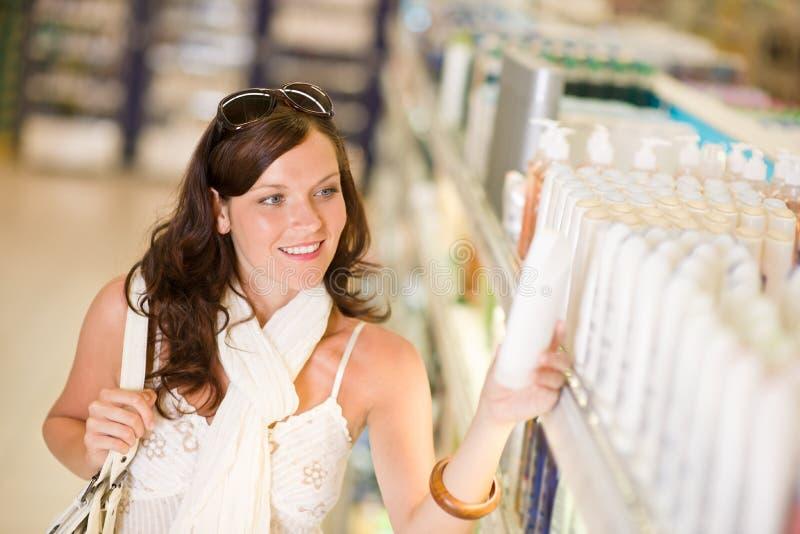 Cosméticos da compra - a mulher de sorriso escolhe o champô foto de stock royalty free