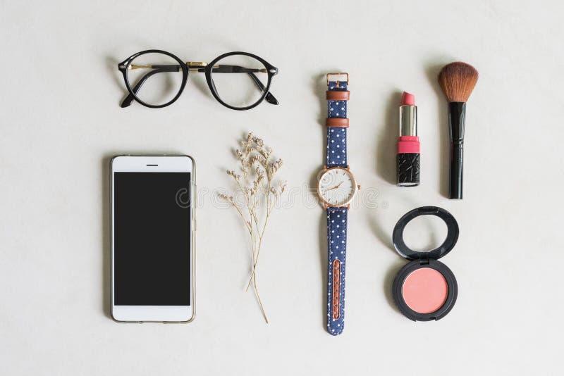 Cosméticos da mulher e artigos da forma com telefone celular fotografia de stock