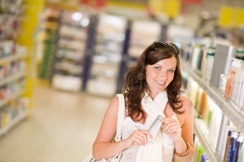 Cosméticos de las compras - mujer con la crema hidratante imagen de archivo libre de regalías