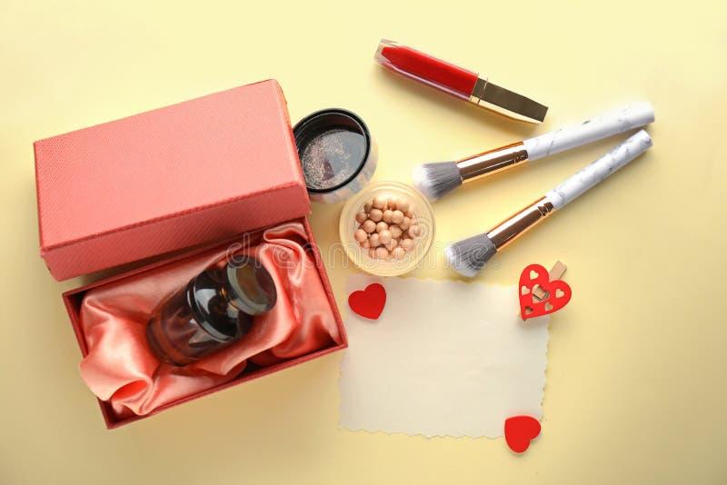 Cosméticos decorativos con perfume y la tarjeta en blanco en fondo ligero fotos de archivo