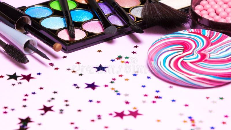 Cosméticos del maquillaje de la celebración de días festivos con la piruleta y el confeti imagen de archivo