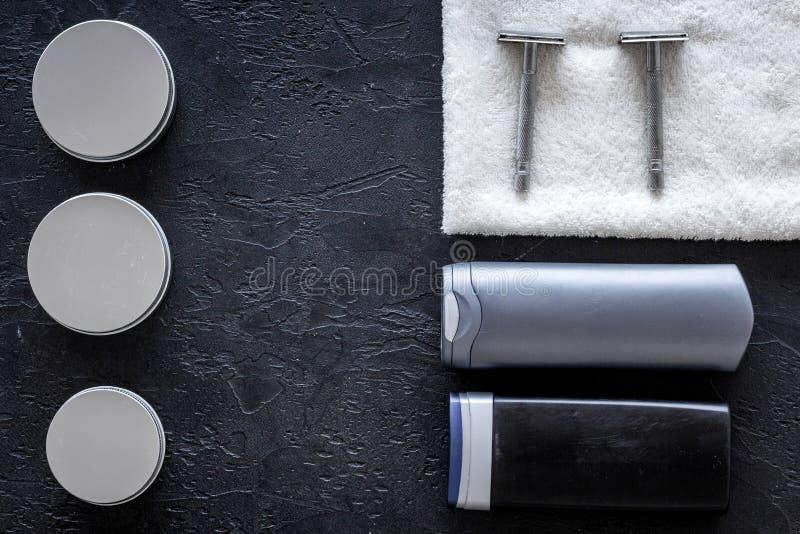 Cosméticos do ` s dos homens para cuidados capilares e rapagem Champô, gel, lâmina, cera no copyspace preto da opinião superior d fotos de stock