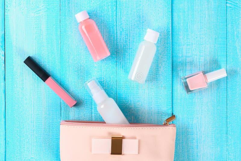 Cosméticos em um saco cosmético cor-de-rosa Brilho do bordo, creme, verniz para as unhas, produtos dos cuidados com a pele em uma imagem de stock royalty free