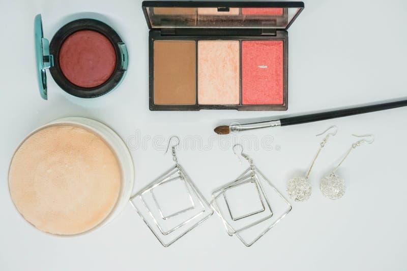 Cosméticos, escova da sombra para os olhos e pó de cara isolados e com os brincos para mulheres fotografia de stock royalty free