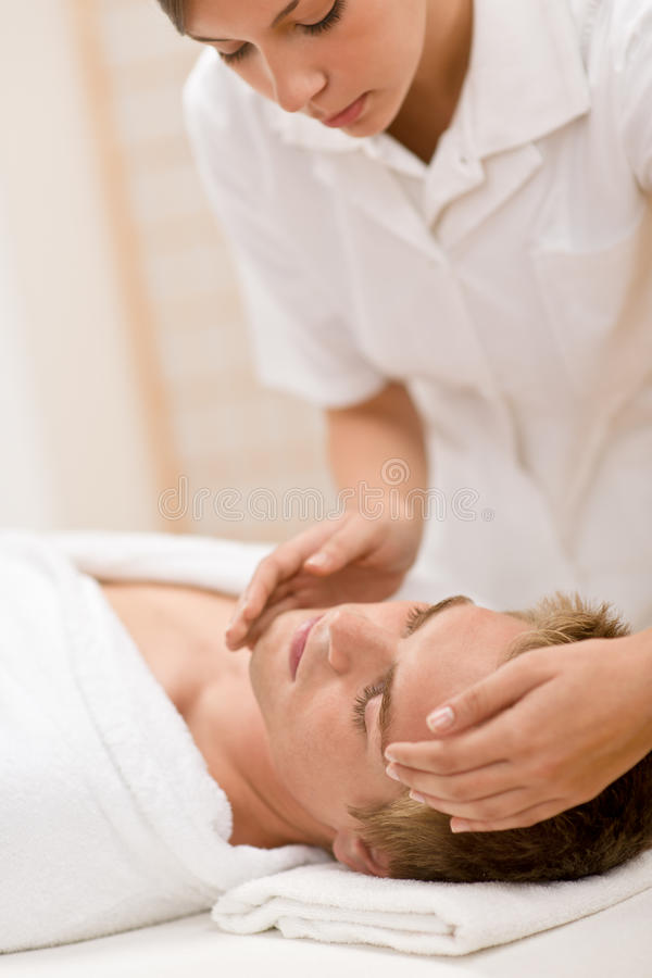 Cosméticos masculinos - masaje facial en salón imagenes de archivo