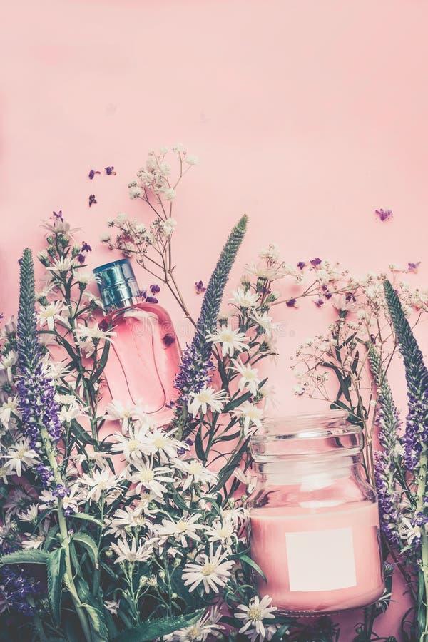 Cosméticos naturais com folhas ervais e flores, etiqueta vazia para o modelo de marcagem com ferro quente no fundo do rosa pastel fotografia de stock