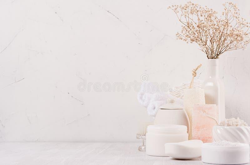 Cosméticos naturais dos termas com creme branco, argila, sal, sabão e as flores secas pequenas no fundo de madeira branco, interi fotografia de stock