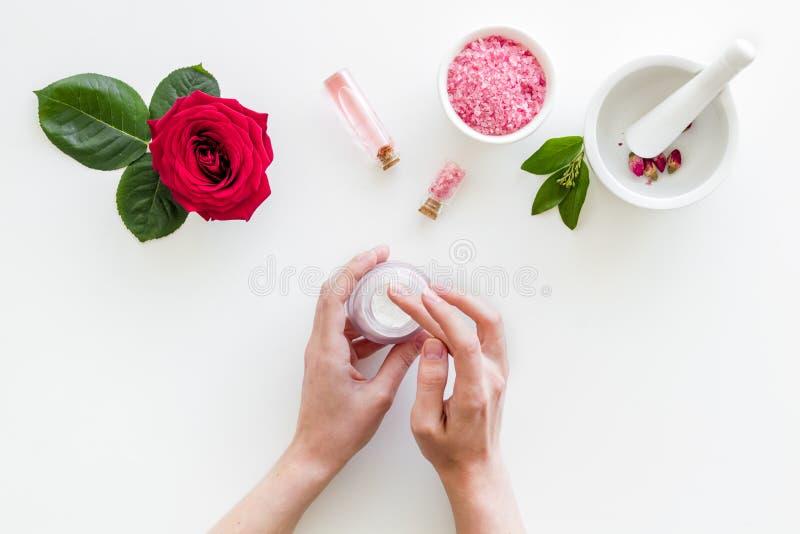 Cosméticos orgánicos naturales con el extracto color de rosa en manos en la opinión superior del fondo blanco imagen de archivo