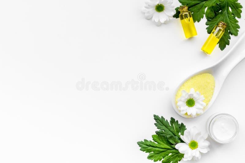 Cosméticos orgánicos naturales del balneario para el cuidado de piel con la manzanilla Sal del balneario, aceite, crema en el esp foto de archivo libre de regalías