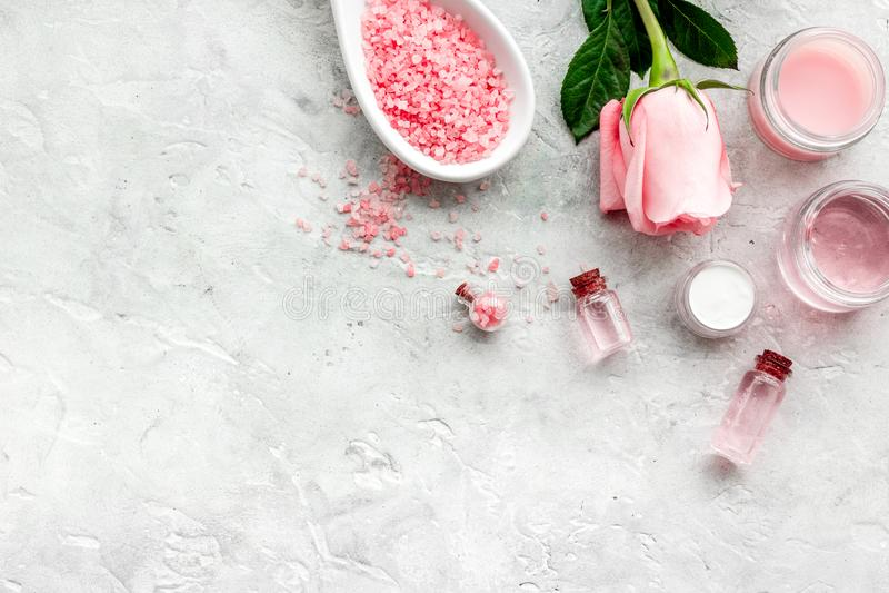Cosméticos orgânicos naturais com óleo cor-de-rosa Creme, loção, sal dos termas no copyspace cinzento da opinião superior do fund foto de stock