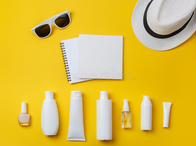 Cosméticos, Panamá y gafas de sol del cuidado de piel del verano en fondo amarillo fotografía de archivo