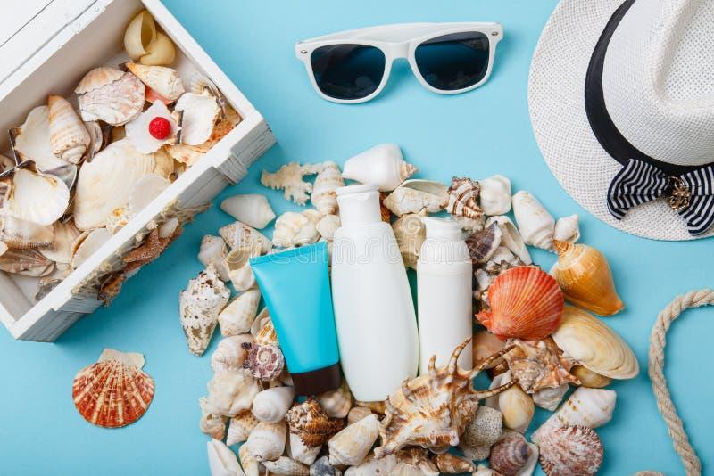Cosméticos, Panamá y gafas de sol del cuidado de piel del verano en fondo azul foto de archivo
