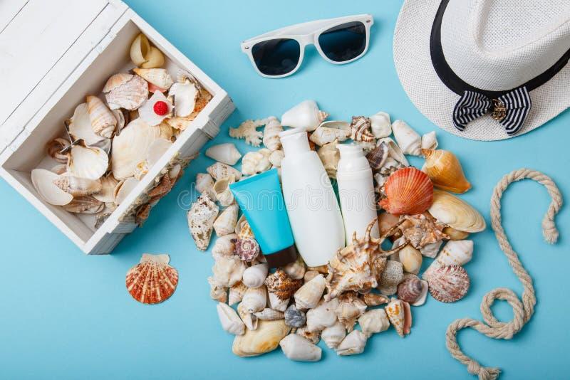 Cosméticos, Panamá y gafas de sol del cuidado de piel del verano en fondo azul imagen de archivo