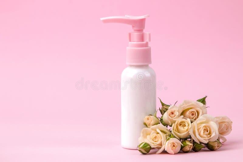 cosméticos para la cara y el cuerpo en botellas rosadas con las rosas frescas en un fondo rosado delicado Spa Visión desde arriba imágenes de archivo libres de regalías