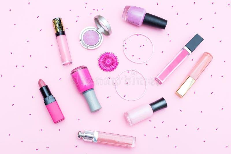 Cosméticos rosados del maquillaje en un fondo rosado Endecha plana fotos de archivo