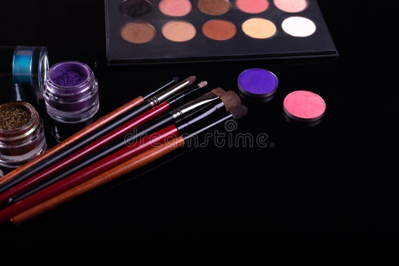 Cosméticos y cepillos profesionales para el maquillaje en un fondo negro foto de archivo libre de regalías