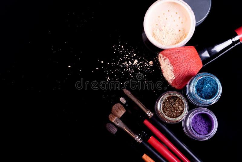Cosméticos y cepillos profesionales para el maquillaje en un fondo negro imagenes de archivo