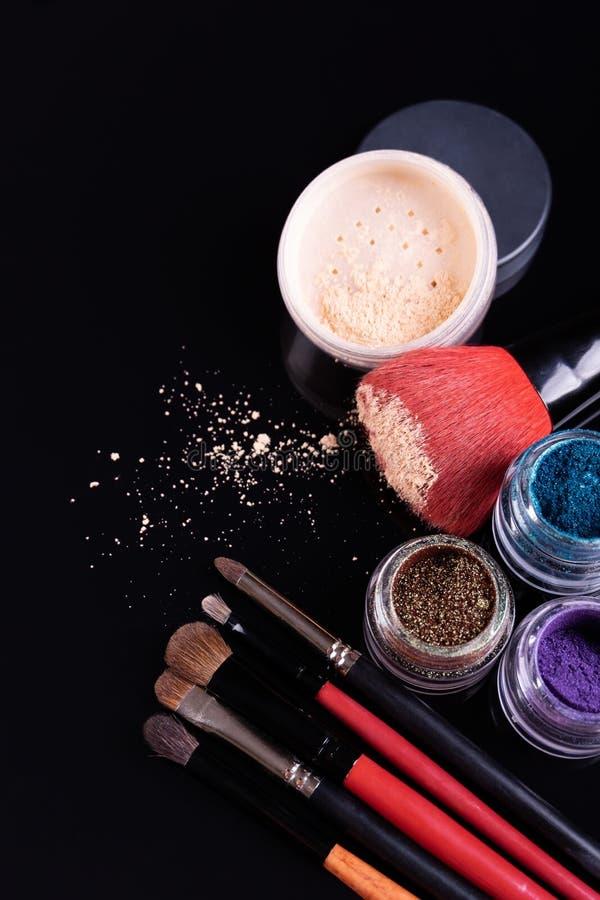 Cosméticos y cepillos profesionales para el maquillaje en un fondo negro imagen de archivo libre de regalías