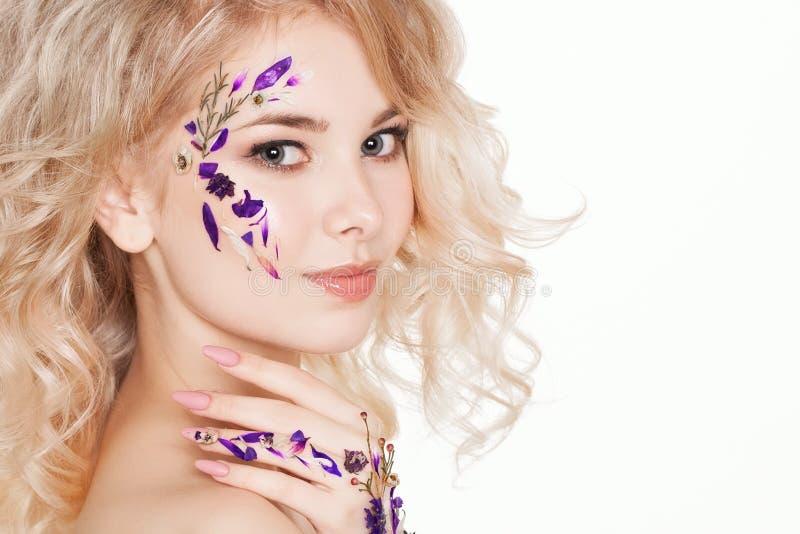 Cosméticos y manicura Retrato del primer de la mujer atractiva con las flores secas en su cara, color en colores pastel del diseñ fotos de archivo libres de regalías