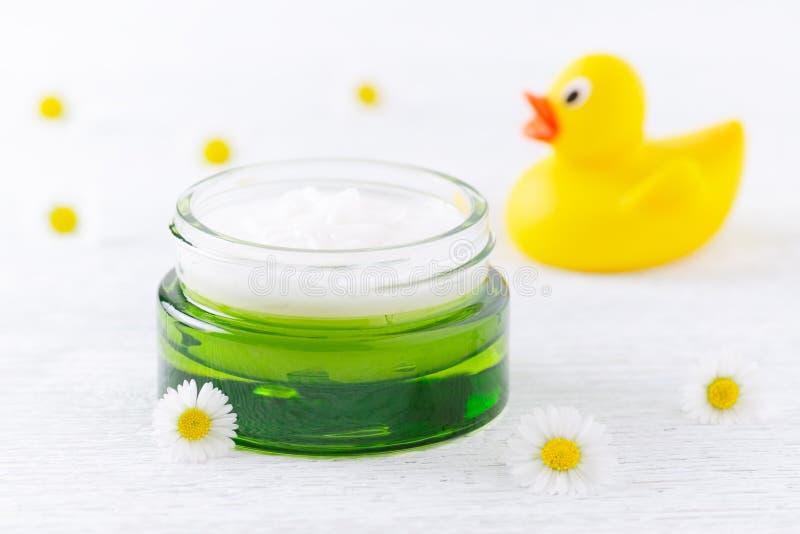 Cosmétique de bébé, crème et fleurs naturels de camomille, un canard, foyer sélectif photos stock