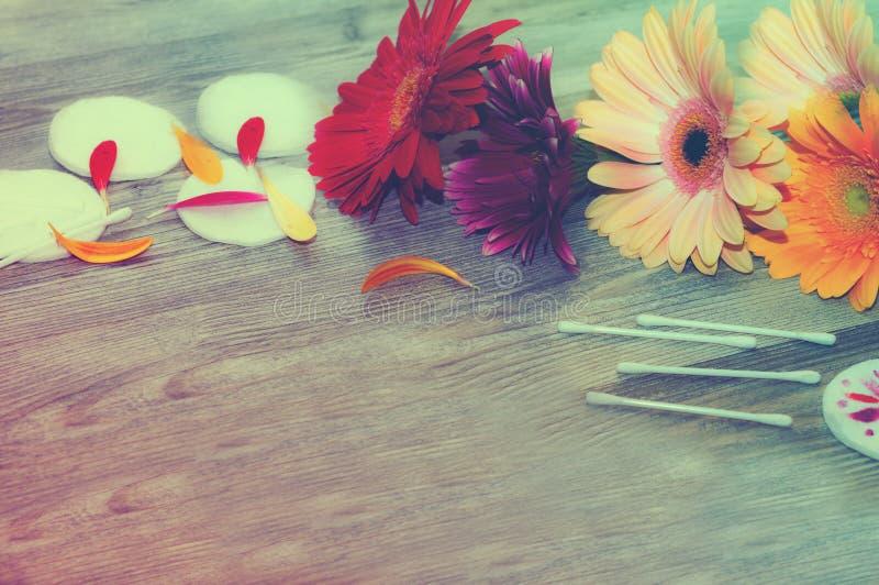 Cosmétique et fleur de bain de station thermale, sur le fond blanc fleurit des tampons de fond, éponge photo libre de droits