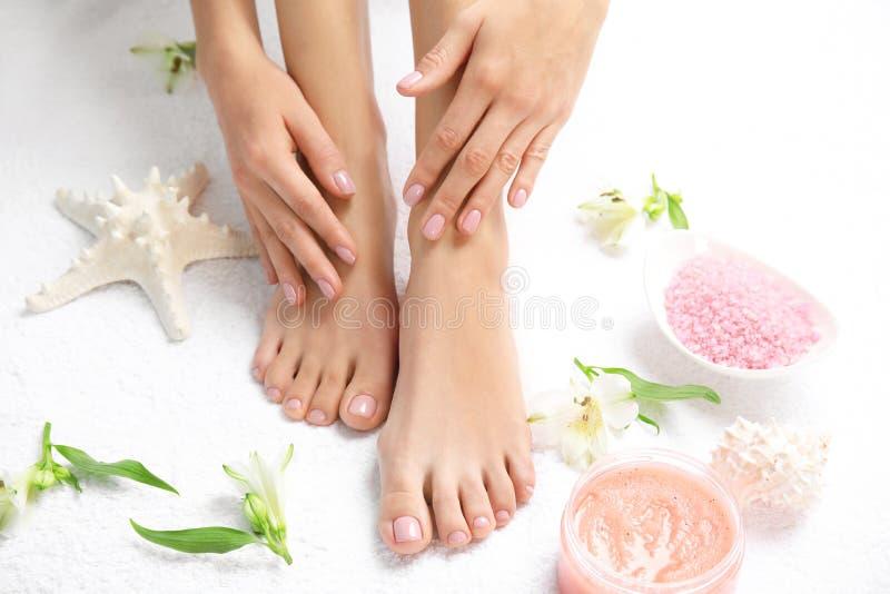 Cosmétique, fleurs et femme touchant ses pieds doux sur la serviette blanche, plan rapproché photos libres de droits