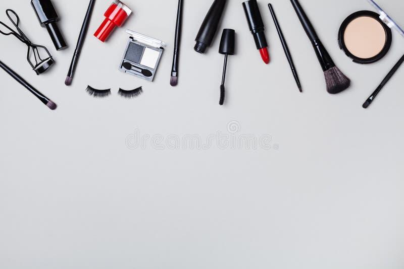 Cosmétique pour le maquillage de femme et produits de beauté sur la vue supérieure grise de table style plat de configuration photographie stock