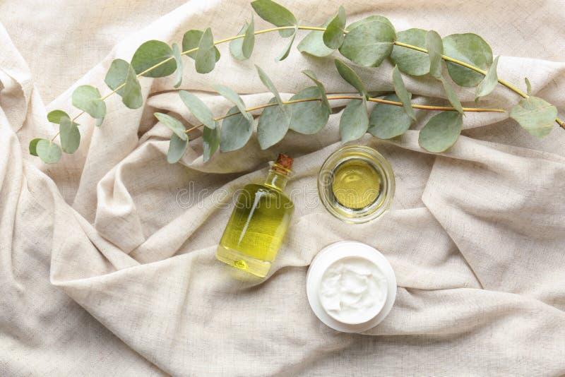 Cosmétiques avec l'extrait d'eucalyptus sur le tissu léger photos stock