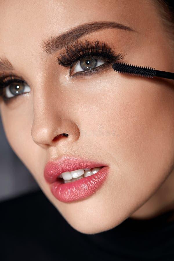 Cosmétiques Belle femme avec le maquillage parfait appliquant le mascara image stock