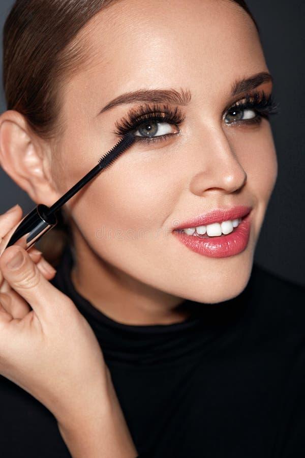 Cosmétiques Belle femme avec le maquillage parfait appliquant le mascara photo stock