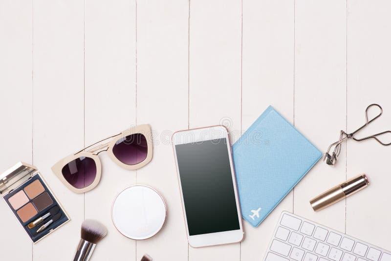 Cosmétiques de femmes et articles de mode sur la table avec l'appareil-photo et le passp photographie stock