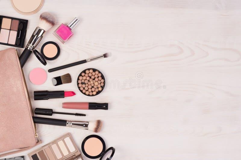 Cosmétiques de maquillage et un sac ouvert sur le fond en bois blanc, vue supérieure avec l'espace de copie images stock