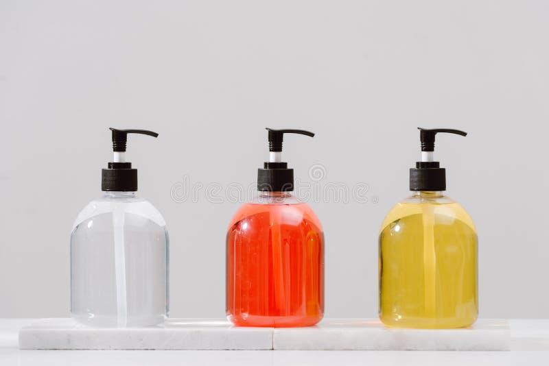 Cosmétiques de station thermale dans des bouteilles en verre brunes sur les bouteilles tableCosmetic concrètes grises avec le gel image libre de droits