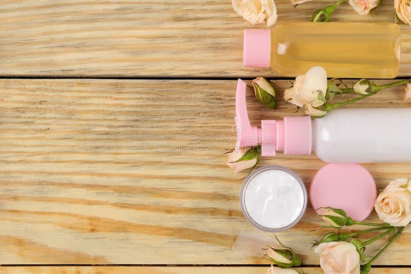 Cosmétiques de visage et de corps dans des bouteilles roses avec les roses fraîches sur un fond en bois naturel écrème et lotion  images libres de droits