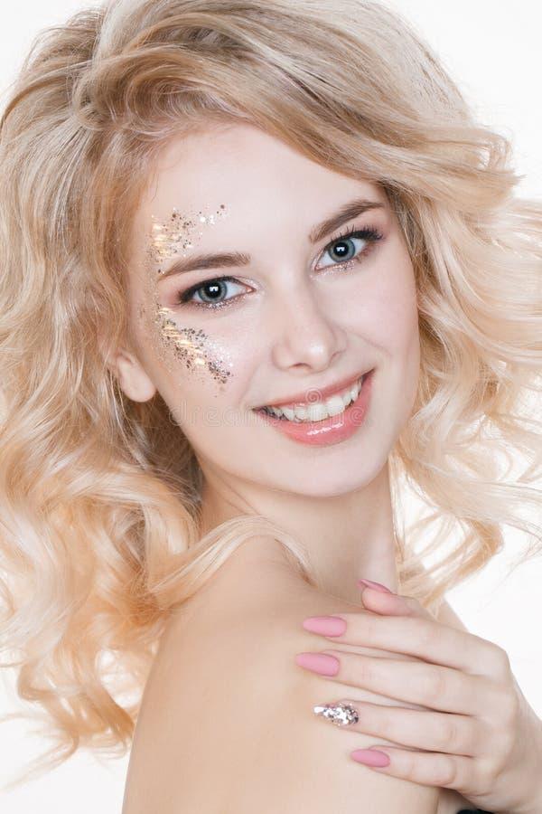 Cosmétiques et manucure Le portrait de femmes de beauté de la jeune femme blonde bouclée avec la manucure en pastel et l'art parf photo stock
