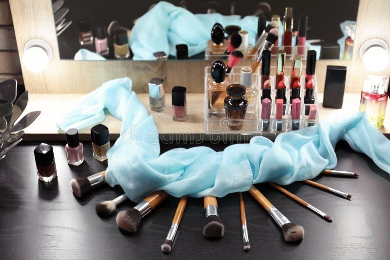Cosmétiques et outils décoratifs sur la coiffeuse photographie stock