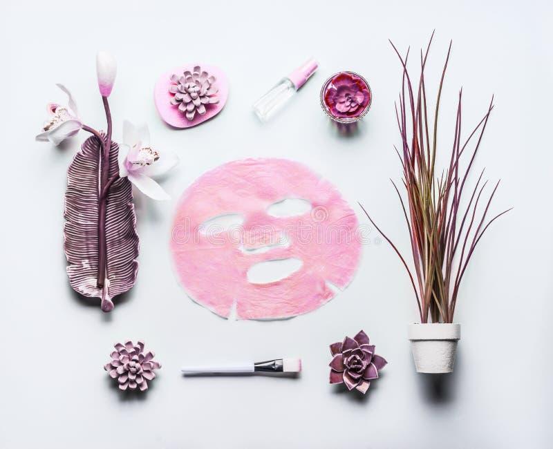 Cosmétiques modernes de soins de la peau composant avec le masque facial rose de feuille L'appartement de beauté s'étendent sur l image libre de droits