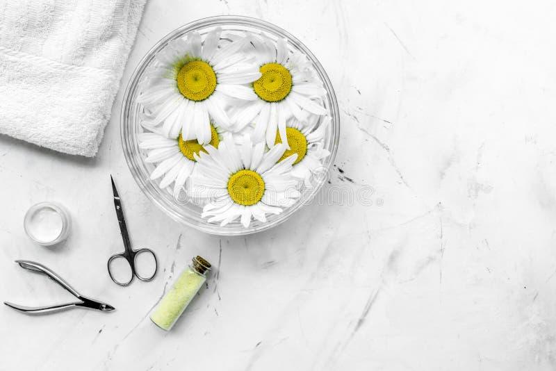 Cosmétiques naturels avec la cuvette de camomilles et d'outils pour la manucure sur l'espace de texture blanc de vue supérieure d photos libres de droits
