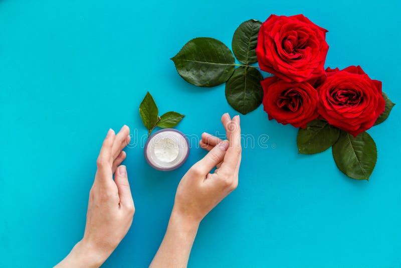 Cosm?tiques organiques naturels avec l'extrait rose dans des mains sur la vue sup?rieure de fond bleu photo libre de droits
