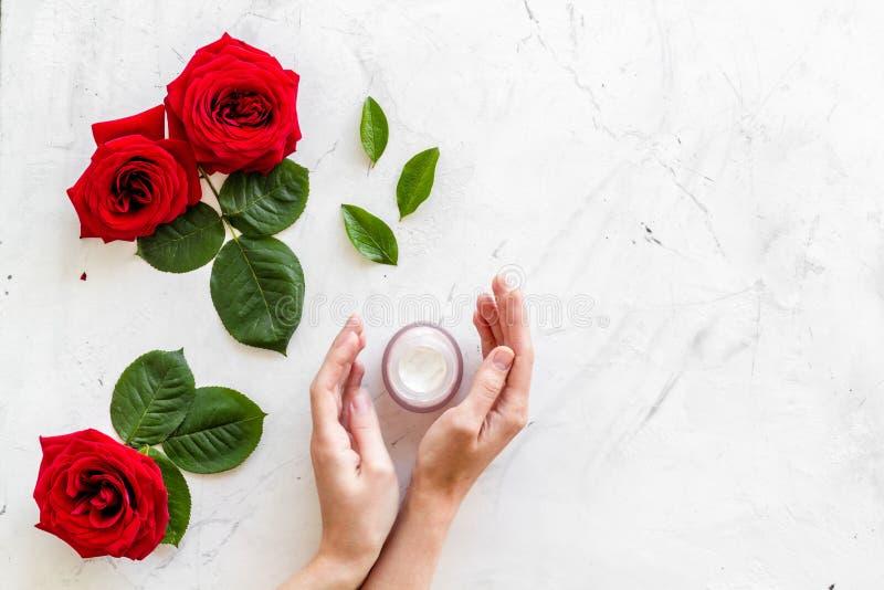 Cosmétiques organiques naturels avec l'extrait rose dans des mains sur le copyspace de marbre blanc de vue supérieure de fond photos libres de droits