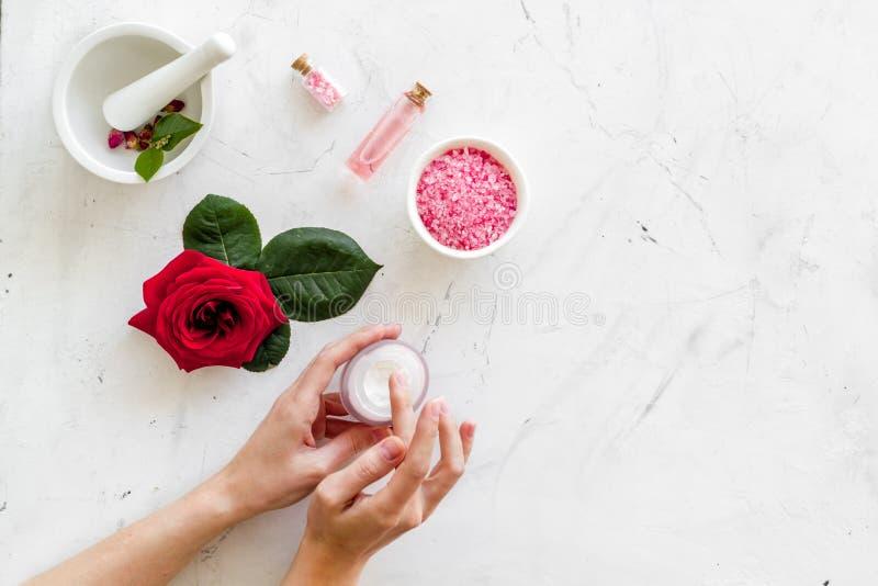 Cosmétiques organiques naturels avec l'extrait rose dans des mains sur le copyspace de marbre blanc de vue supérieure de fond image libre de droits
