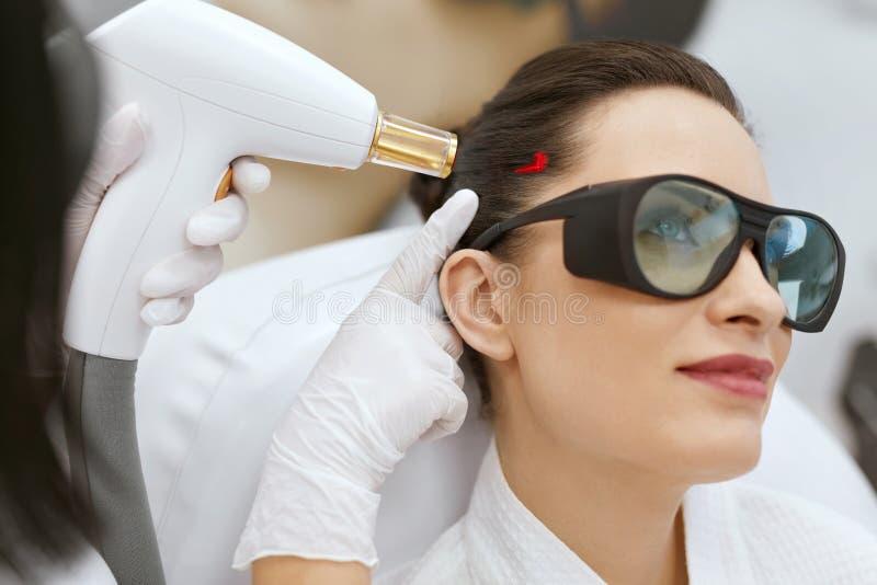 cosmétologie Femme au traitement de stimulation de laser de croissance de cheveux photographie stock libre de droits