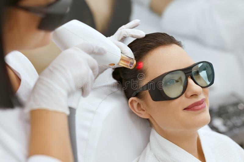 cosmétologie Femme au traitement de stimulation de laser de croissance de cheveux photos libres de droits