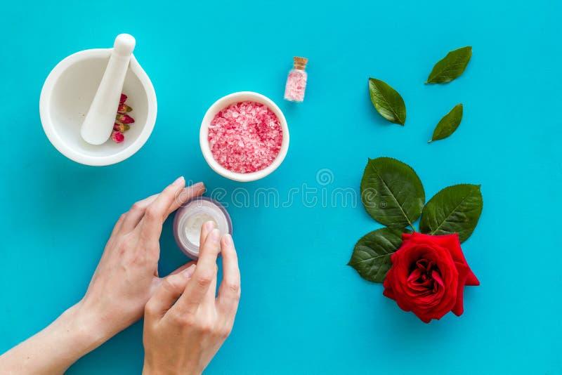 Cosm?tiques organiques naturels avec l'extrait rose dans des mains sur la vue sup?rieure de fond bleu photos libres de droits